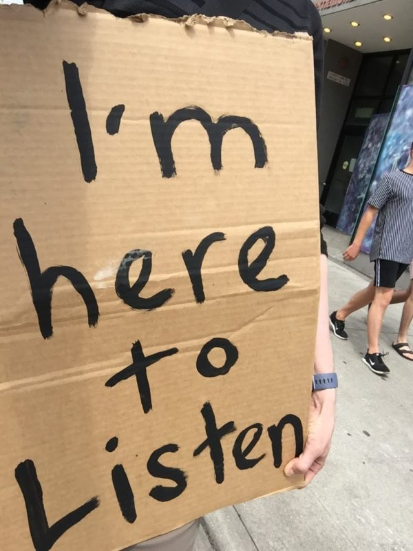 """holding a sign in a protest march that says """"I'm here to listen"""""""